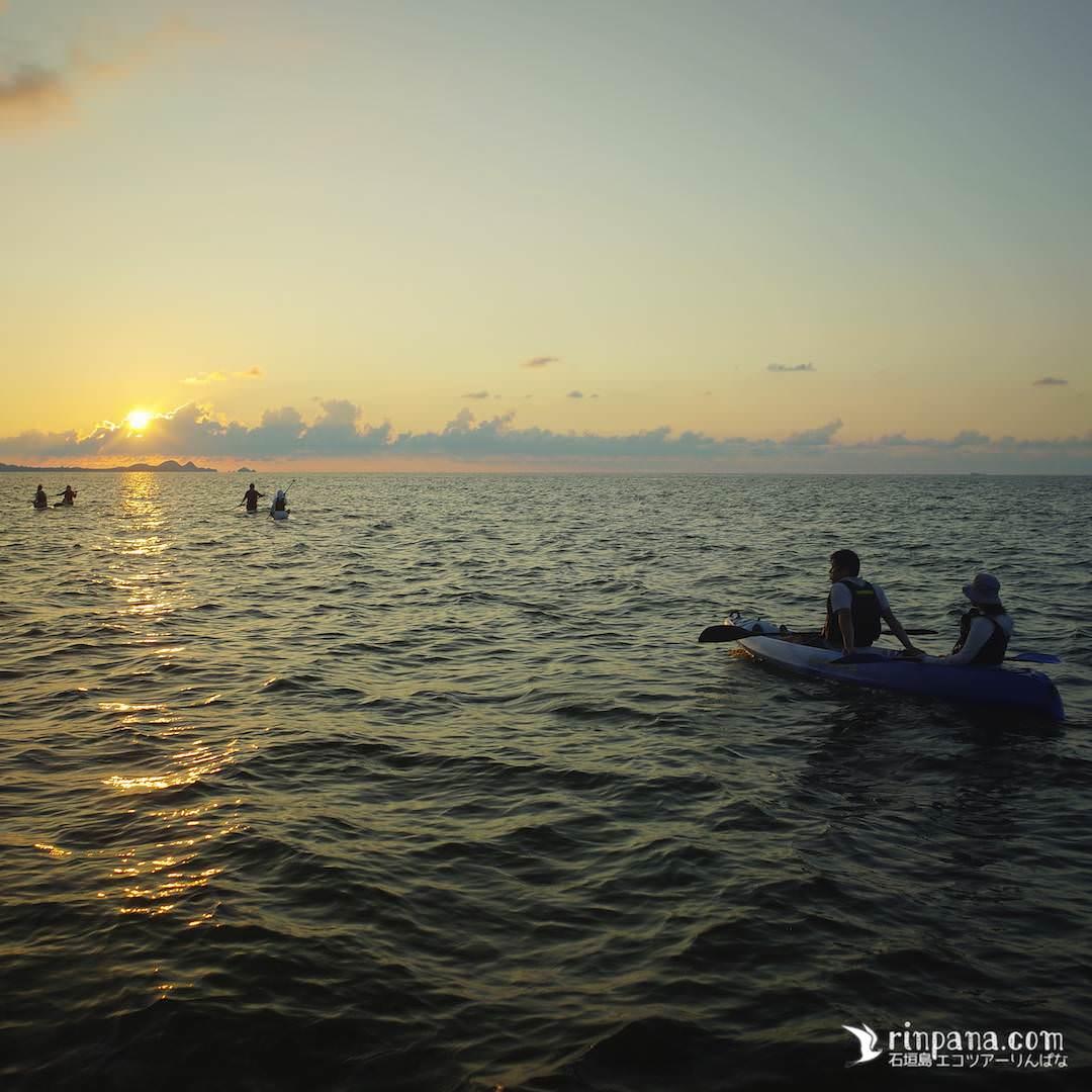 カヌーの上から夕陽を眺める写真