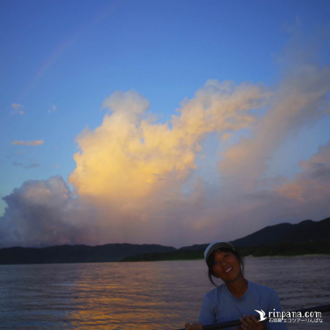 カヌーから夕陽をながめる女性の写真