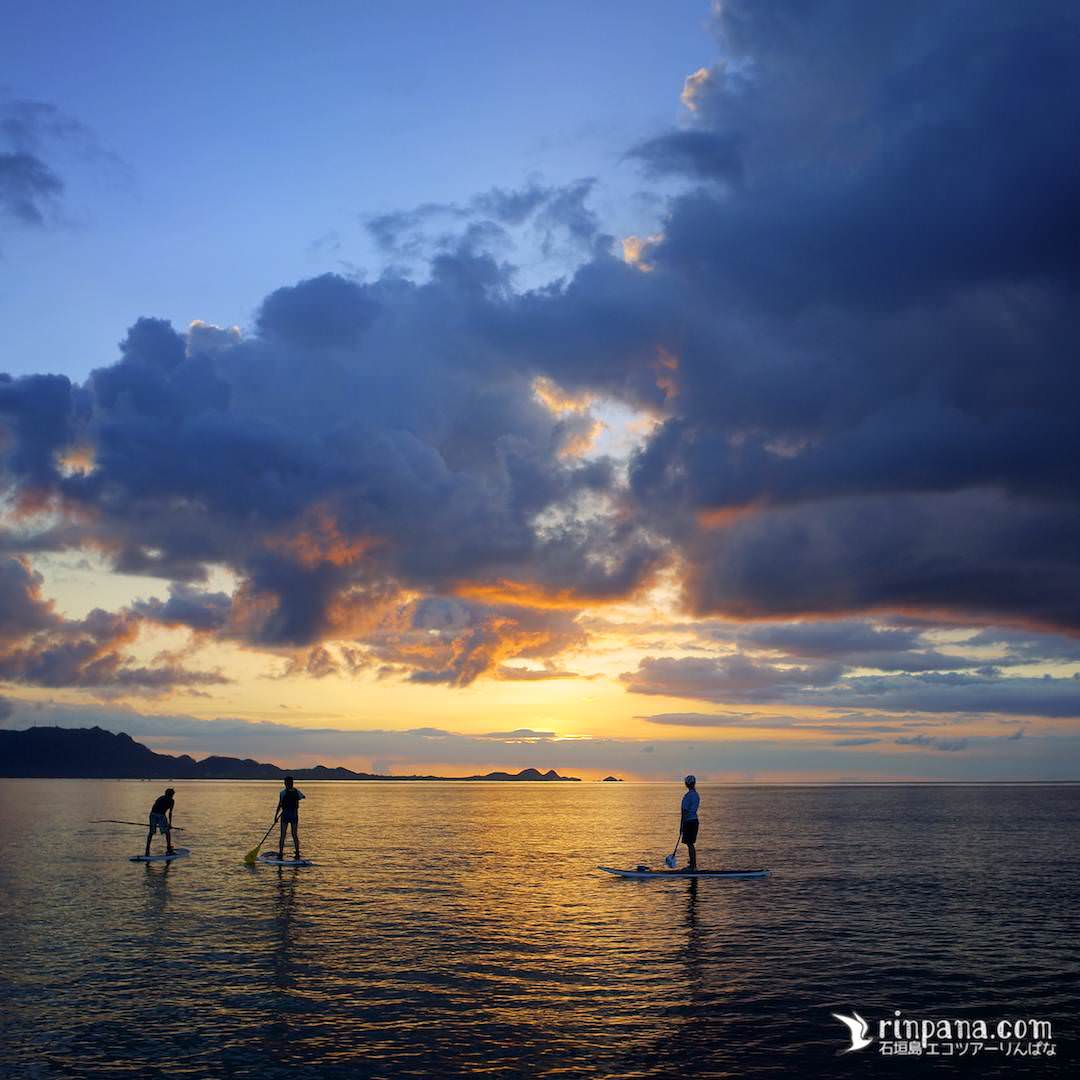 SUPに乗って夕陽を海の上で見る写真
