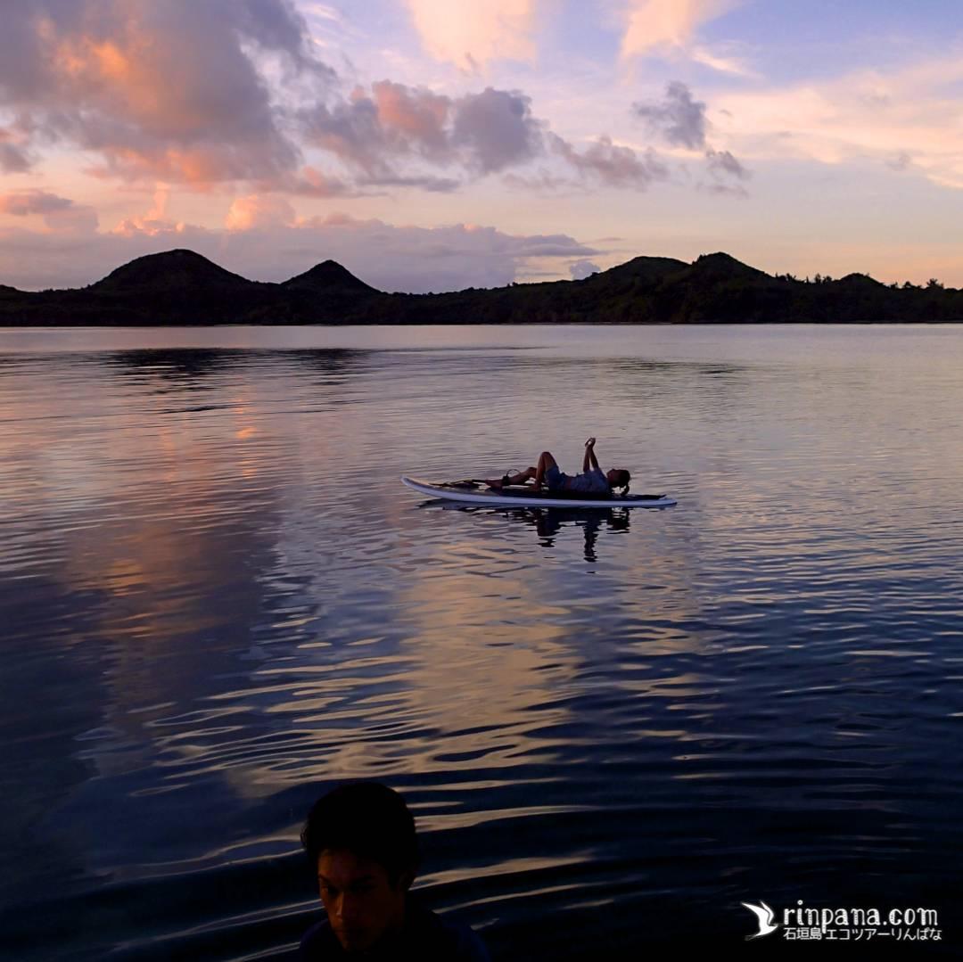 SUPボードの上に寝転びのんびり夕陽を眺める