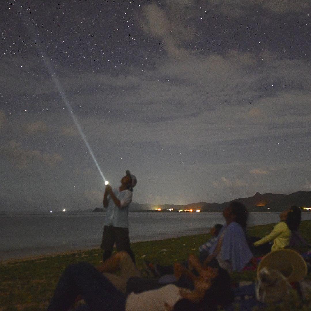 星空ガイドがライトで星座を解説している
