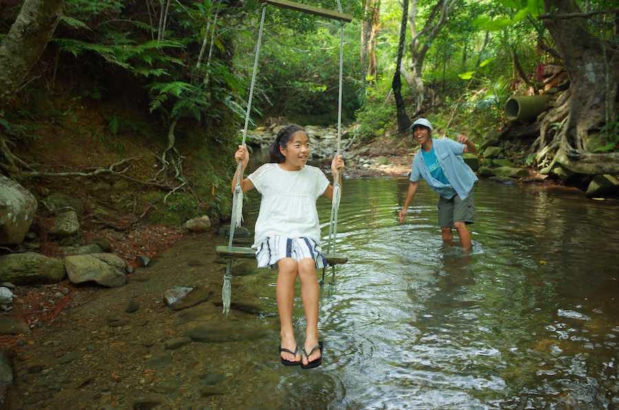 川にかかったぶらんこで遊ぶ女の子