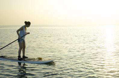 SUPでサンゴ礁を上から眺める女性