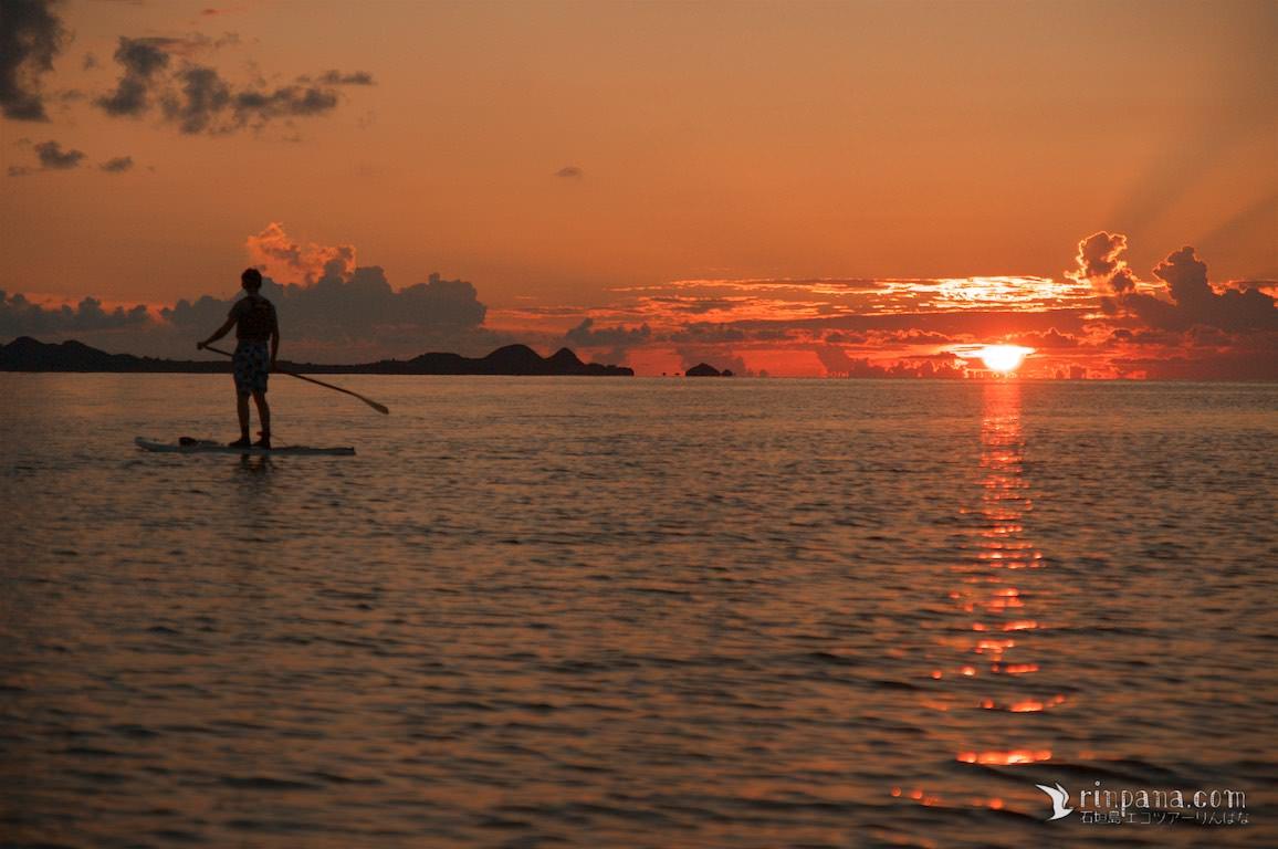 水平線に夕陽が沈む中をSUPを漕ぐ