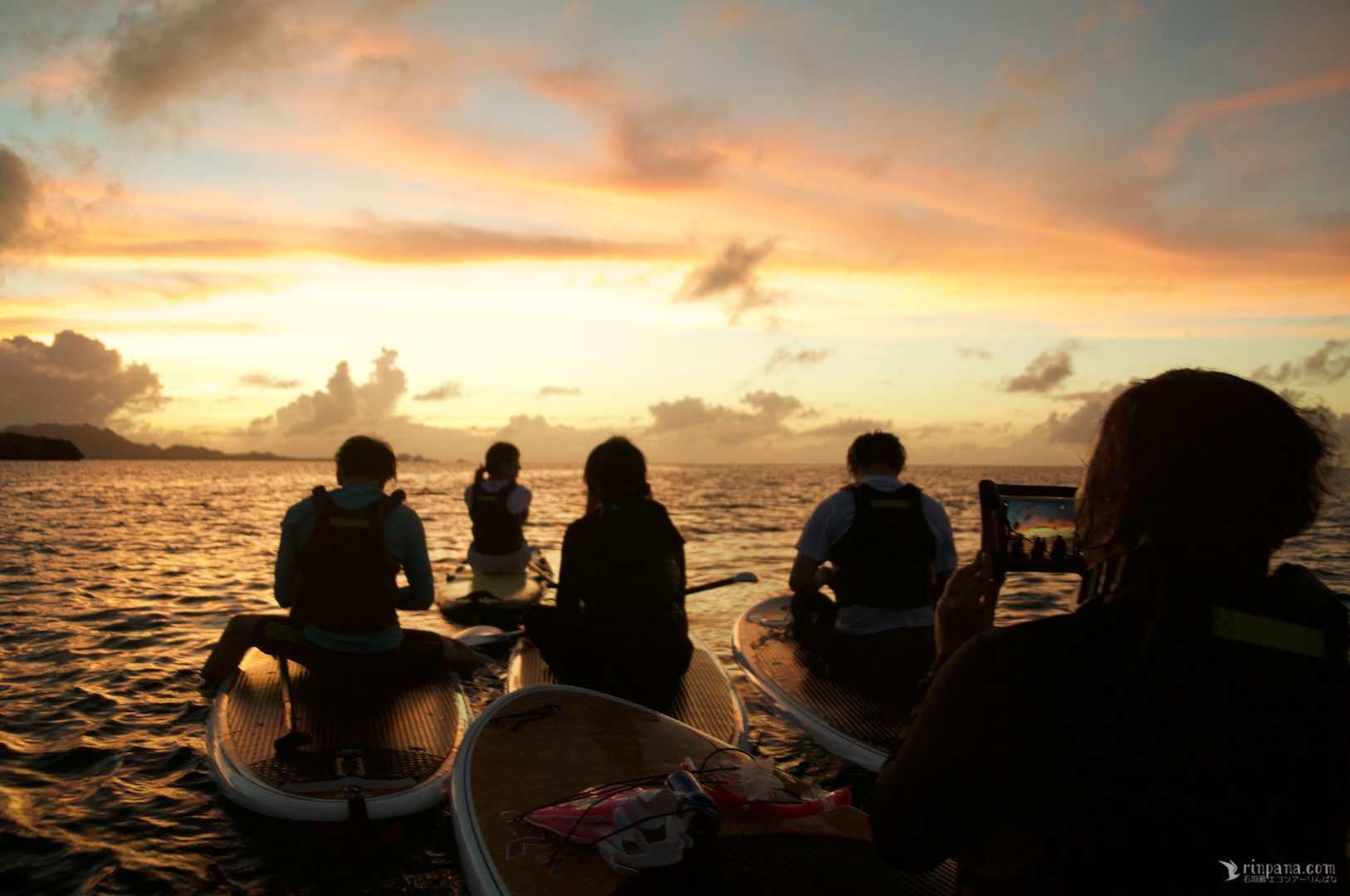 海の上でSUPに乗り夕陽を写真に撮る