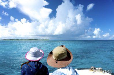 離島航路を進む船の船首に座る女性